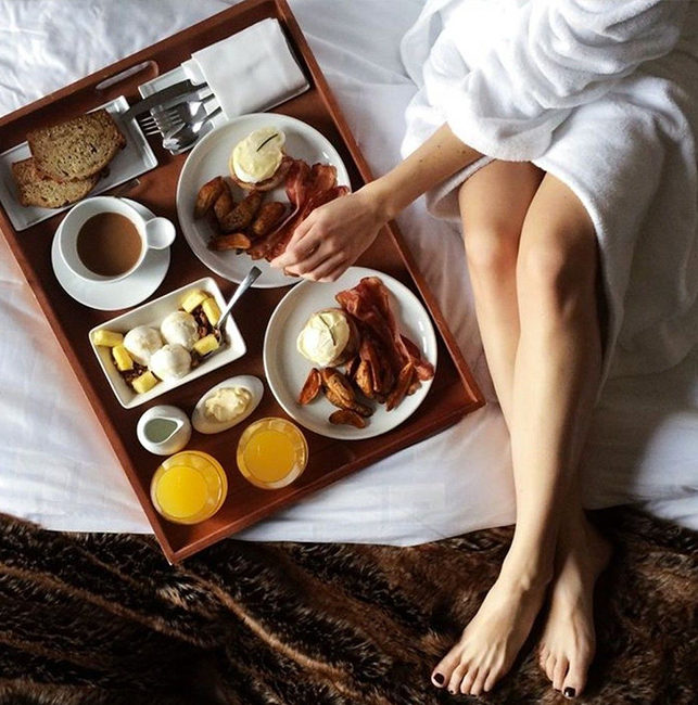 Woman in robe enjoying breakfast in bed at our Rancho Santa Fe, CA 5 Star resort