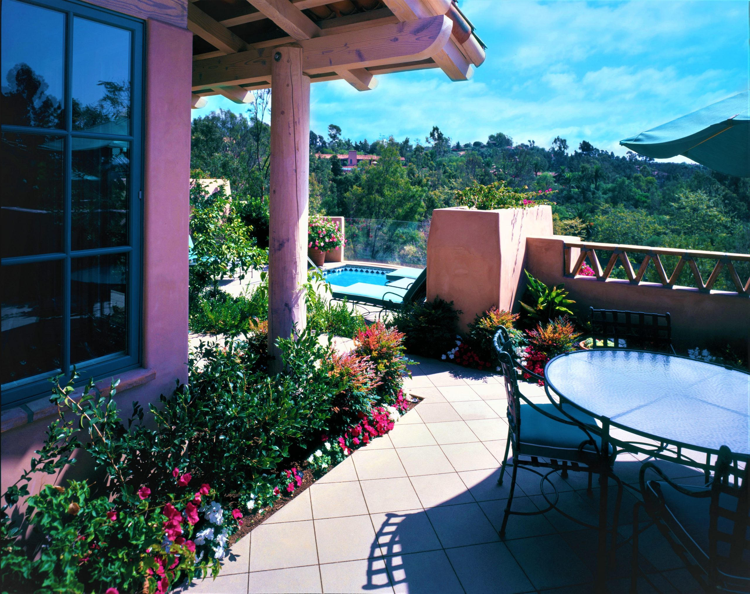 Accessible San Diego Olive Grove hotel suite patio overlooking spacious resort grounds with trees, flowers, pool