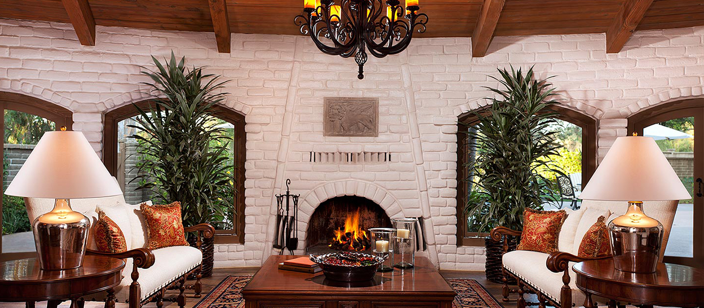 San Diego hotel suite fireplace with living area with coffee table, two couches and plants