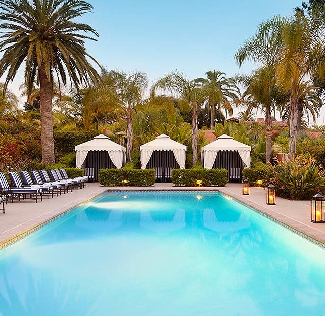 Luxury San Diego resort outdoor pool with chaise lounge chairs, private cabanas, palm trees