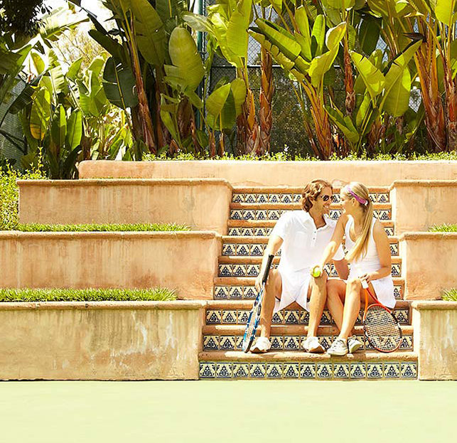 Couple sitting on stairs next to tennis courts holding tennis ball and tennis rackets at 5 star hotel in San Diego