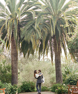 Groom carrying bride between two palm trees at Rancho Valencia luxury San Diego resort & spa