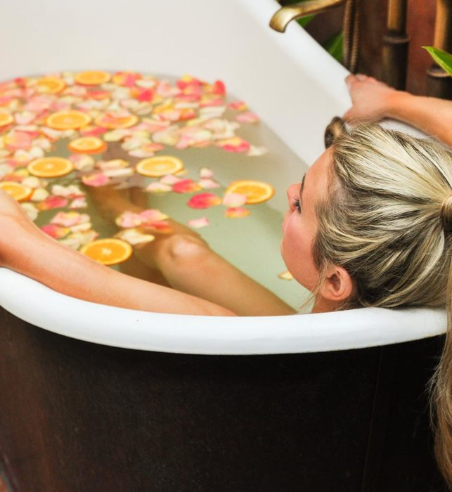 Woman soaking in tub with orange slices and rose petals at luxury San Diego spa resort