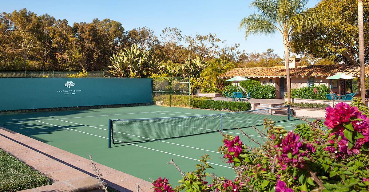 Hard tennis court surrounded by lush foliage at San Diego tennis resort, Rancho Valencia