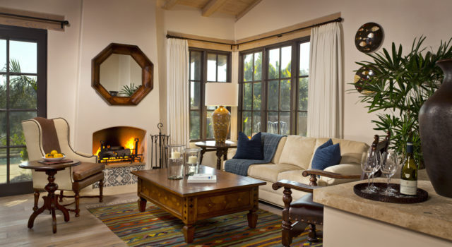 Rancho Valencia Suite living room with fireplace, private patio, couch, chair and large windows