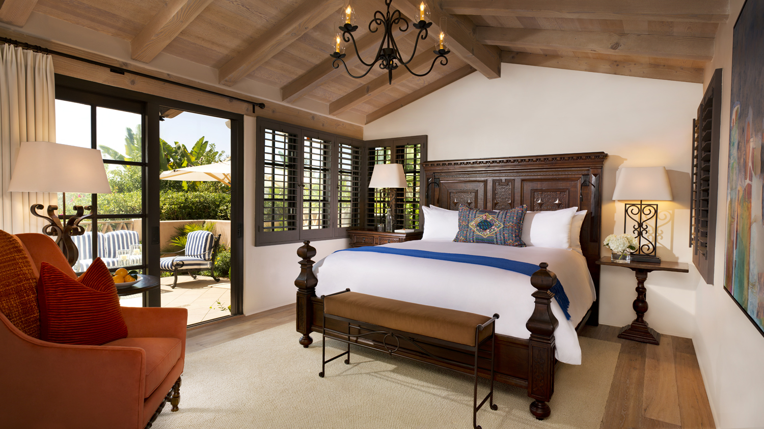 Large king bedroom with doors to private patio, chair in Valencia hotel suite at Rancho Valencia