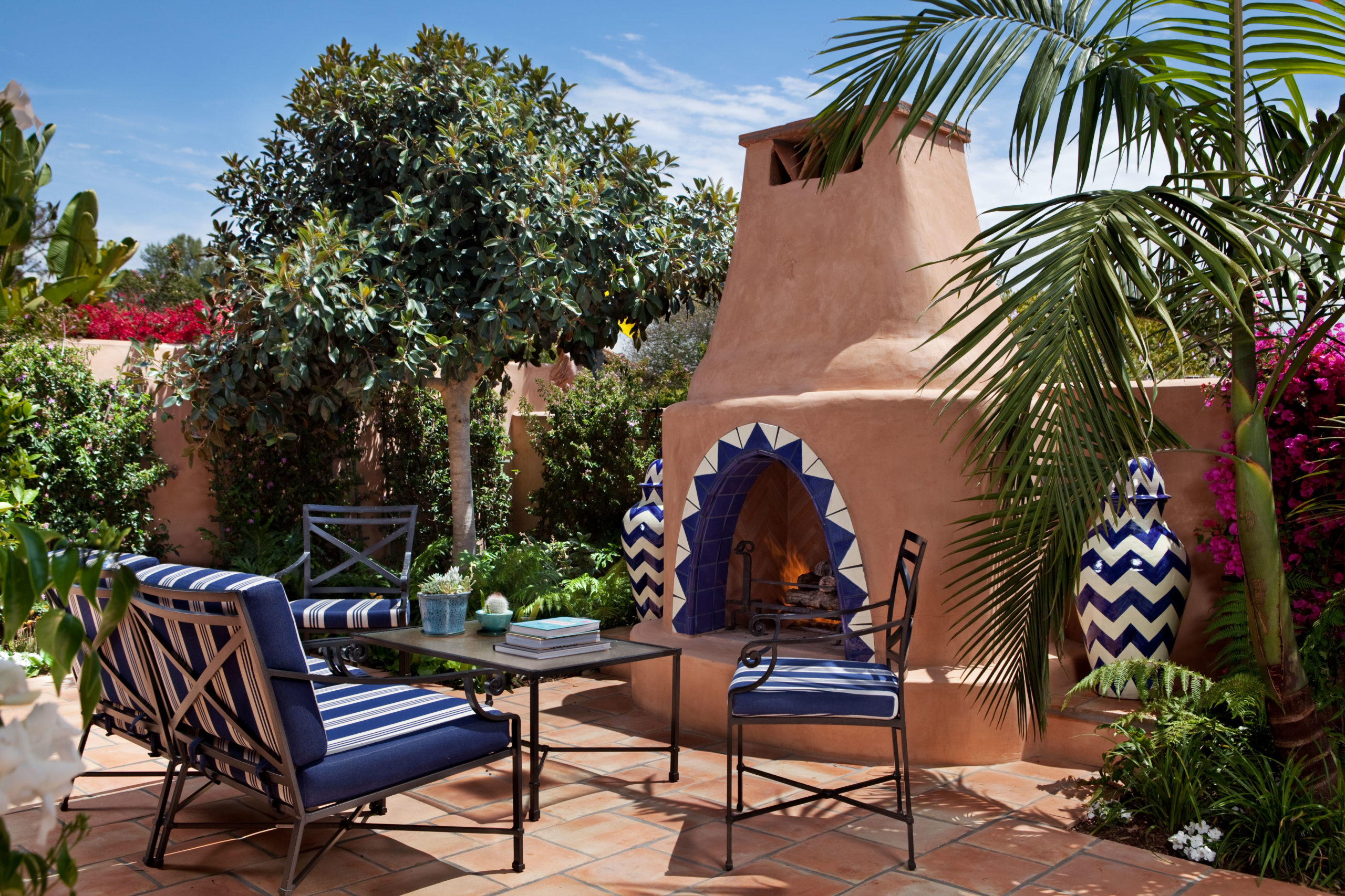 Large outdoor patio with outdoor fireplace, outdoor furniture and lush foliage at luxury San Diego resort, Rancho Valencia