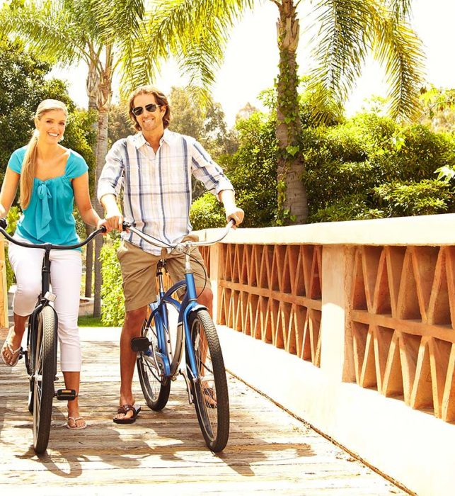 Man and woman riding complimentary bikes over bridge at luxury San Diego 5 Star resort, Rancho Valencia