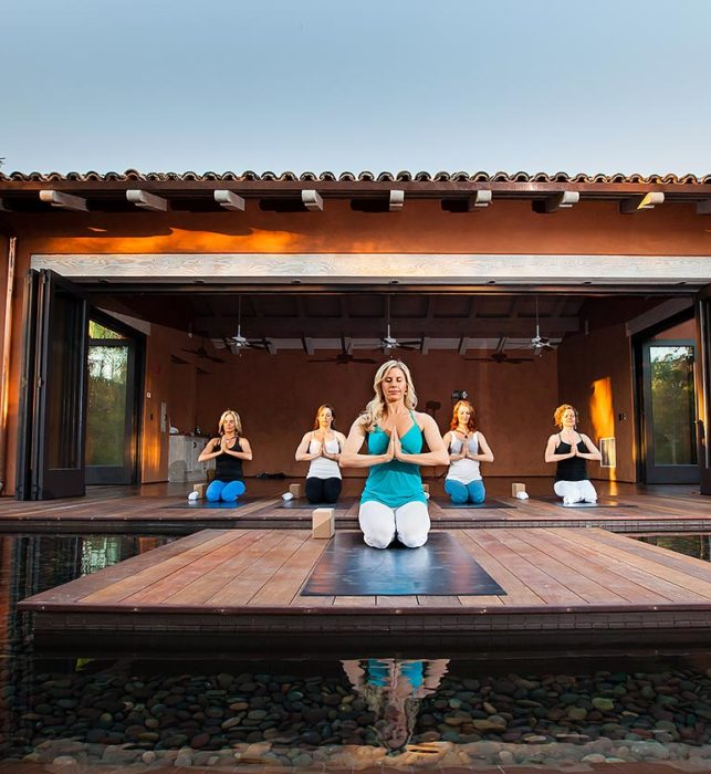 Women doing yoga in yoga pavilion at Rancho Valencia Spa resort in Southern California