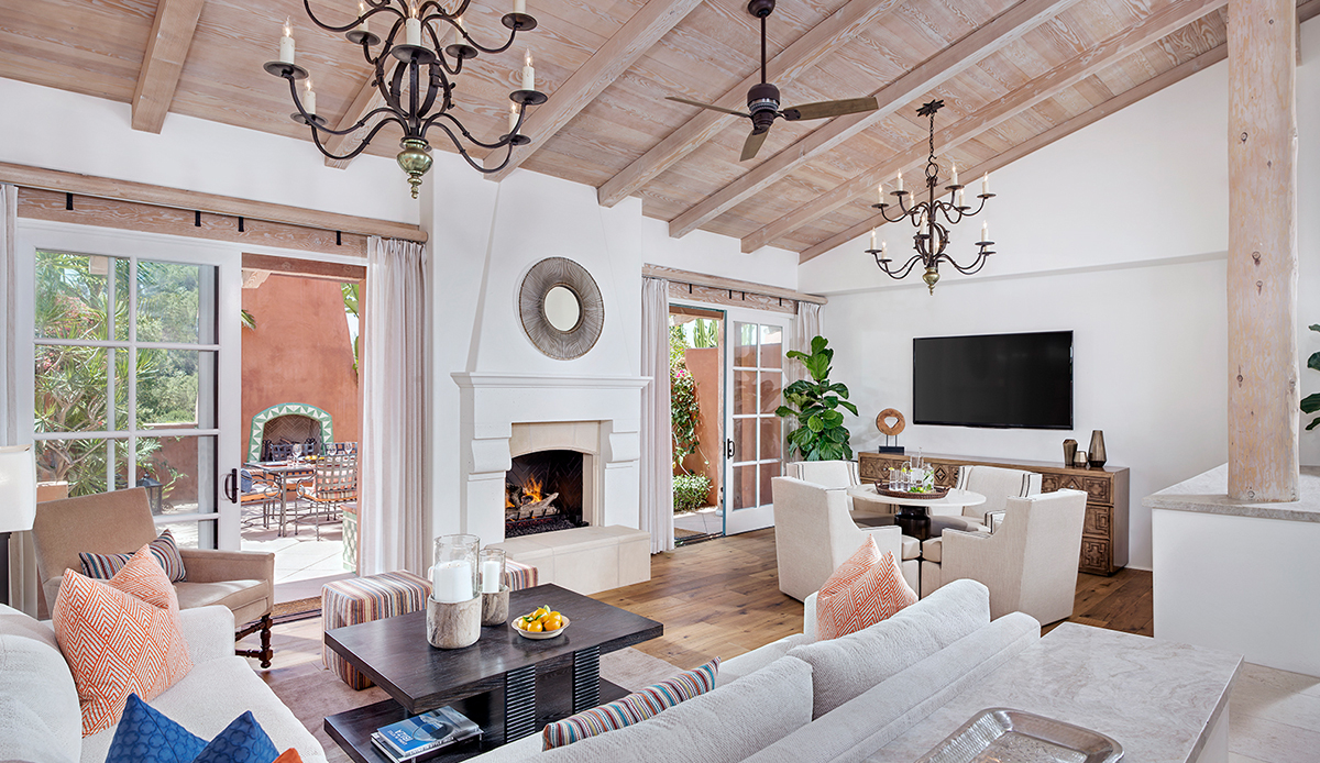 Interior of San Diego luxury resort villa with couches, dining area and sliding doors to private patio