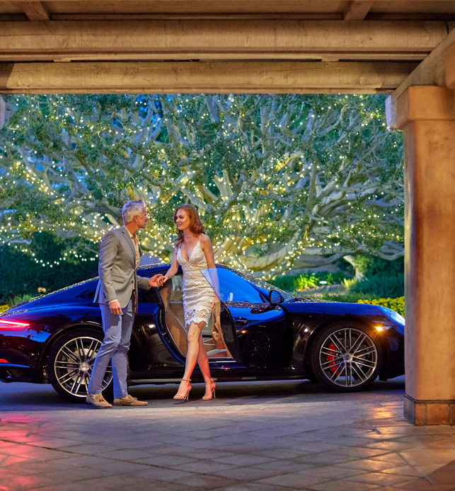 Man and woman valeting Porsche at entrance to Rancho Valencia San Diego resort