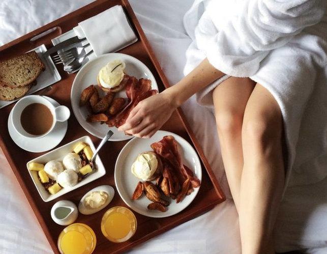 Woman in robe enjoying breakfast in bed at our Rancho Santa Fe, CA 5 Star resort