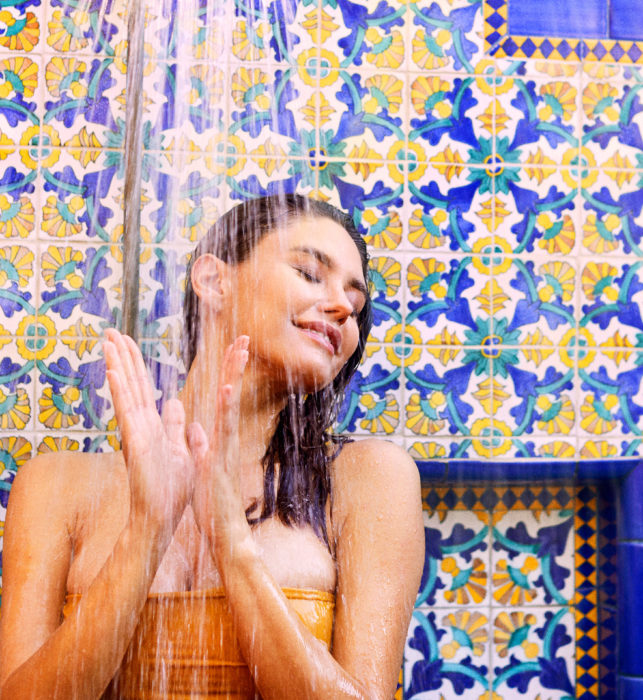 Woman standing under outdoor shower, spanish tiles at Rancho Valencia San Diego resort