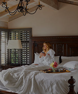 Woman in robe drinking coffee with breakfast in bed at luxury San Diego resort and spa, Rancho Valencia