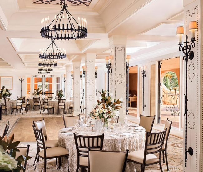 Large ballroom San Diego wedding reception with round tables, chandeliers, flowers