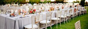 San Diego outdoor wedding reception tables with flowers, candles, chairs on lawn at Rancho Valencia