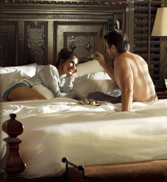 couple lounging in bed at the rancho valencia